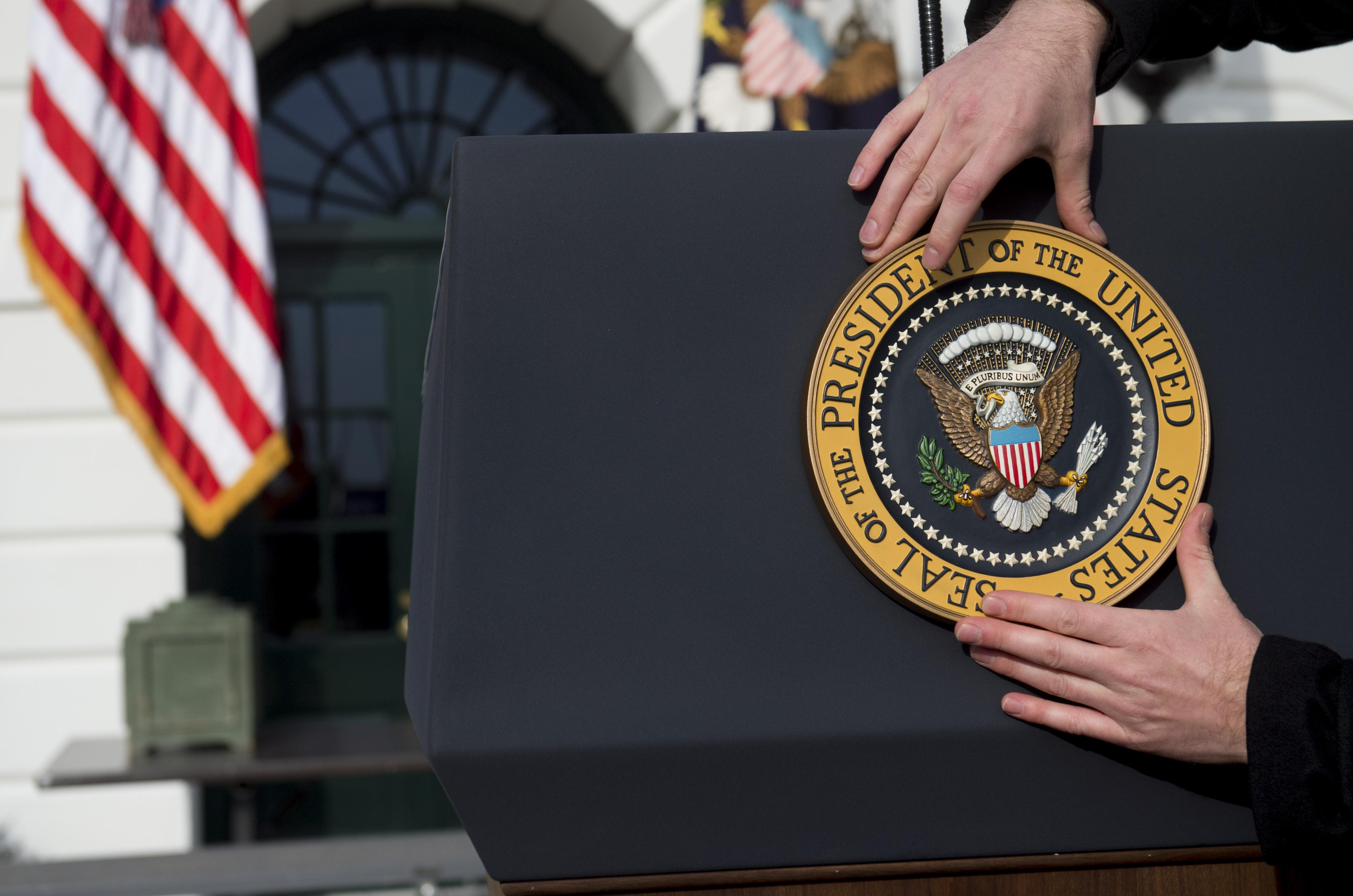A staff member places the Presidential Seal on a podium on the South Lawn of the White House.