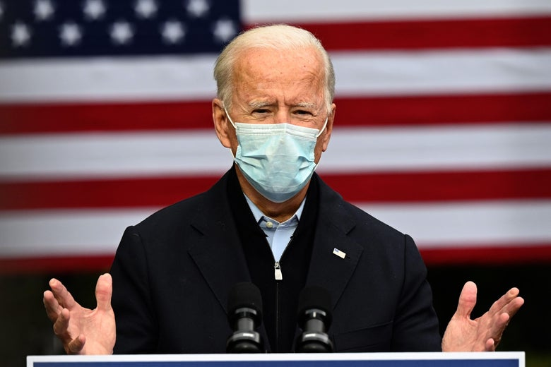 Joe Biden stands in front of a flag, wearing a surgical mask and speaking from a lectern.