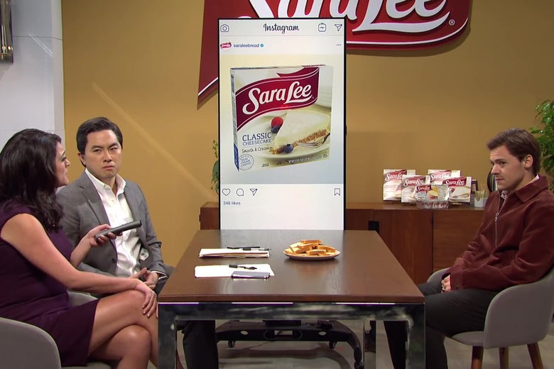 On one side of a conference table sit Cecily Strong and Bowen Yang, in suits, glaring at a despondent Harry Styles on the other side of the table. On the wall behind them is a projector displaying a post from the Sara Lee Instagram account.