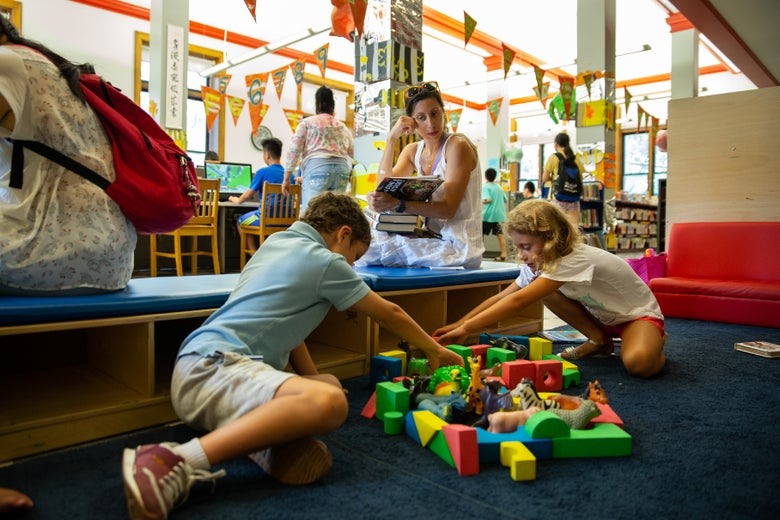 A boy and a girl play with blocks and animal toys on the floor as their mother looks on.
