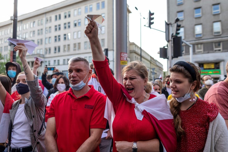 A crowd of people dressed mostly in red on a street. A couple people are holding paper planes in the air.