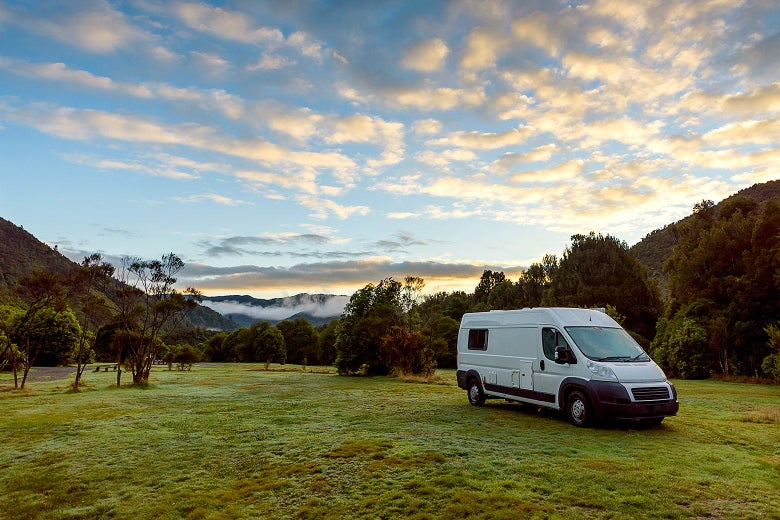 A camper van parked on grass at sunrise.