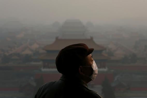 A tourist wearing the mask looks at the Forbidden City as pollution covers the city on January 16, 2013 in Beijing, China.