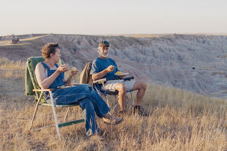 A still from Nomadland: Frances McDormand as Fern and David Strathairn as Dave sit on lawn chairs in front of a scenic backdrop.