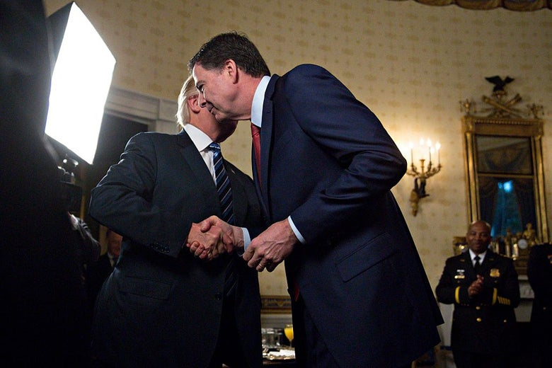 Trump and Comey shake hands as Trump speaks into Comey's ear.