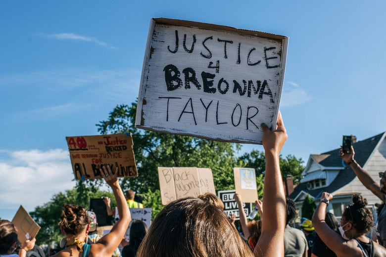 "People march in a protest against police brutality and racism. One holds up a sign that reads ""Justice 4 Breonna Taylor."""