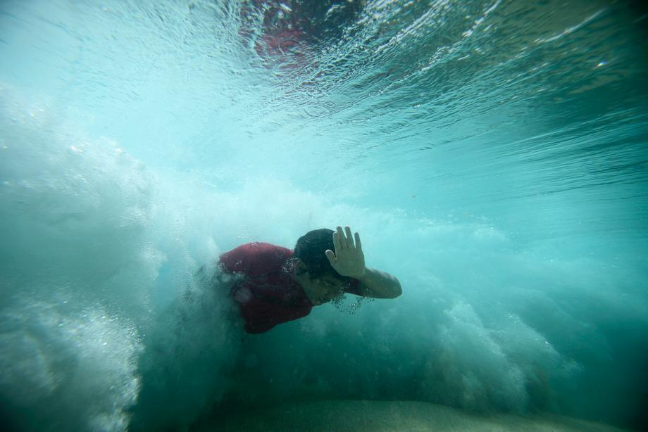 A bodysurfer punches through a wave at the Ehukai sandbar near the surf break known as 'Pipeline' on the North Shore of Oahu, Hawaii on March 20, 2013.
