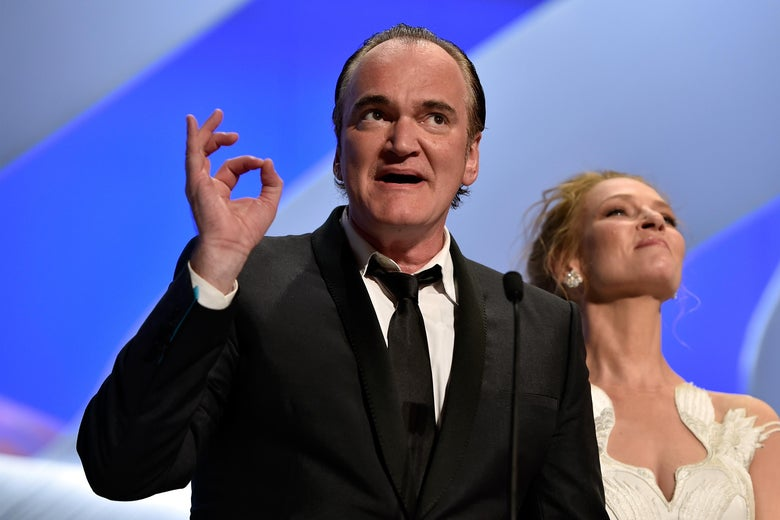 Quentin Tarantino holds his thumb and index finger together as Uma Thurman stands behind him