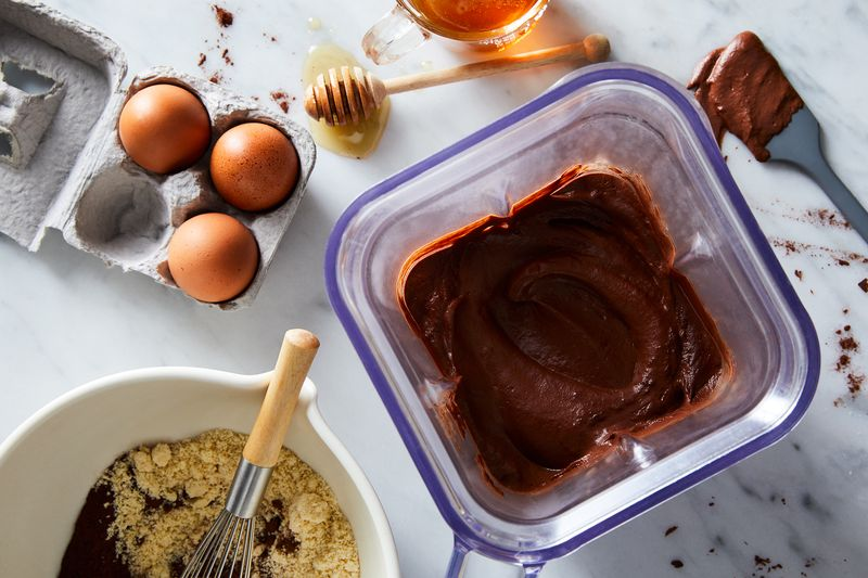 Bird's eye view of chocolate mix in a square pitcher, a partially mixed bowl of mix and sugar, an opened quarter of a egg carton with 3 eggs inside and honey pooling around a mixer