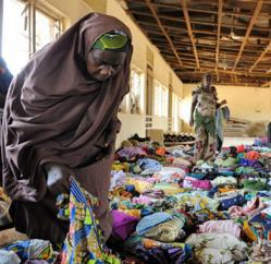 A woman examines clothes donated by humanitarians to be distributed to displaced people at Hajj Camp in Kaduna on April 26, 2011.