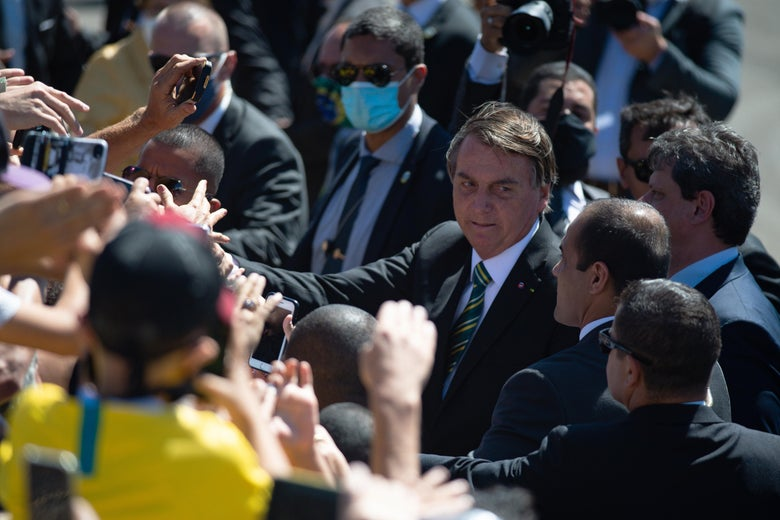 Bolsonaro, not wearing a mask, greets a crowd of his supporters