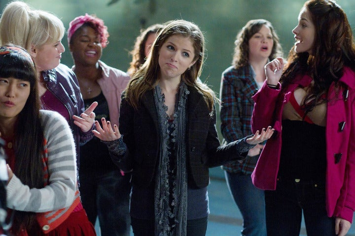 Anna Kendrick stands in a group of women shrugging her shoulders.
