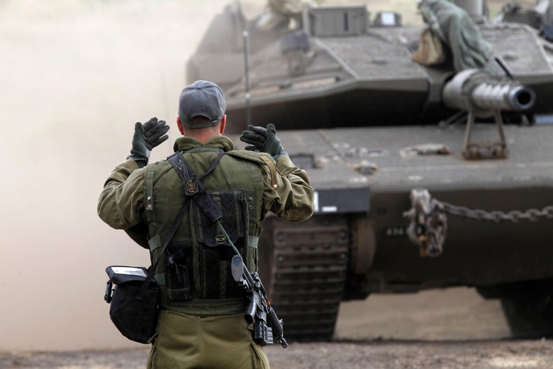 An Israeli soldier waves on a Merkava Mark IV tank.