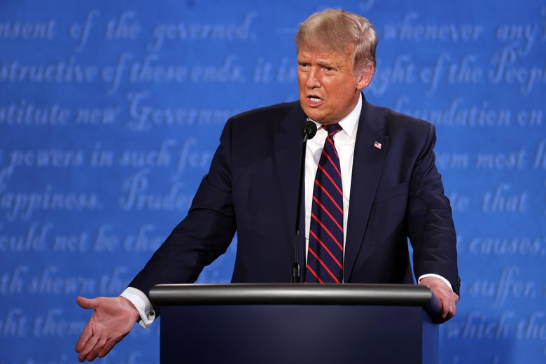 Trump gestures with his right hand as he stands at the podium on stage, answering a debate question.