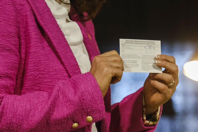 A woman shows holds her vaccine card in her hands.