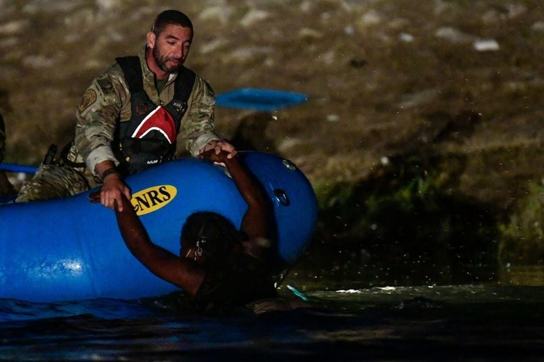 A man in a camouflage uniform in a blue inflatable boat holds the arms of a woman who is submerged up to her chest in water at night.