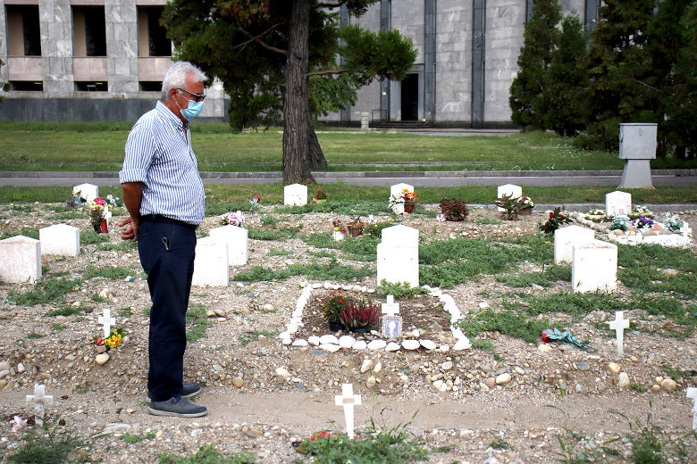 A man examines a makeshift grave made of rocks.