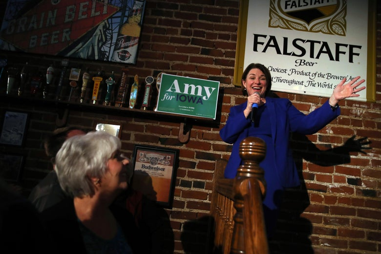 Amy Klobuchar, at right, speaks near a railing with her hands up. To her left, people watch her underneath beer taps.