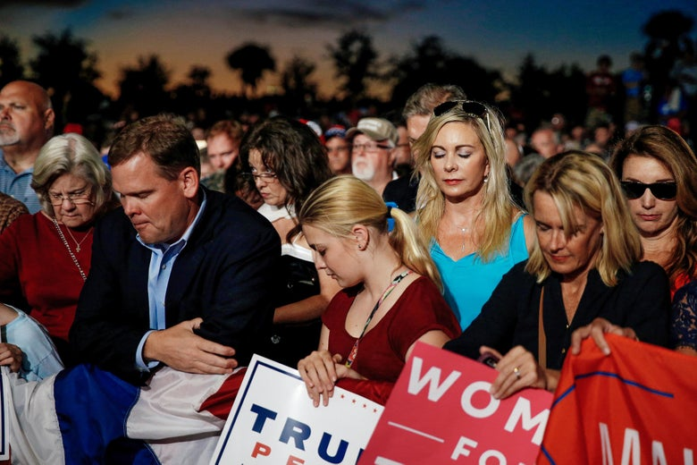 Supporters bow their heads in prayer before a Trump rally.