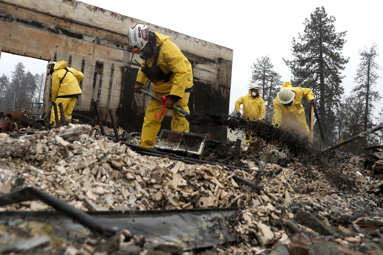 Search and rescue crews dig through the burnt remains of a business as they search for human remains on November 21, 2018 in Paradise, California.