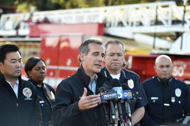 Los Angeles Mayor Eric Garcetti speaks into a microphone in front of a fire truck.