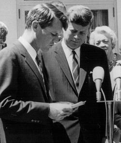 President John F. Kennedy listens as his brother Robert speak at a White House ceremony.