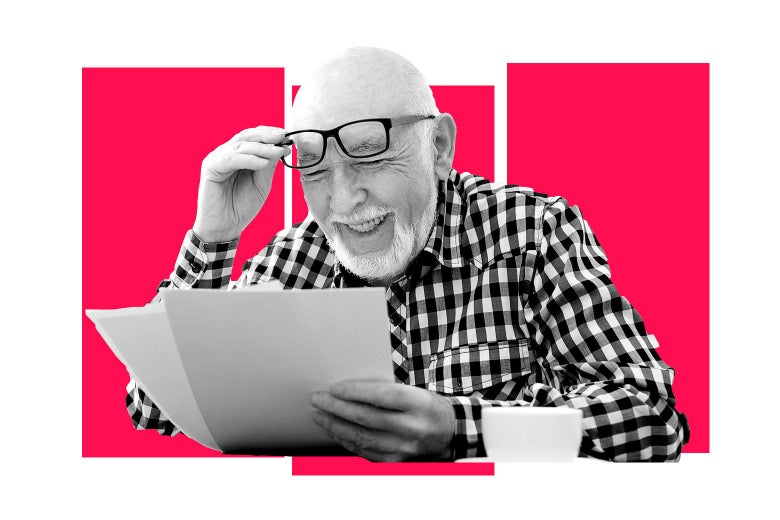A man lifting his glasses and reading papers while laughing.