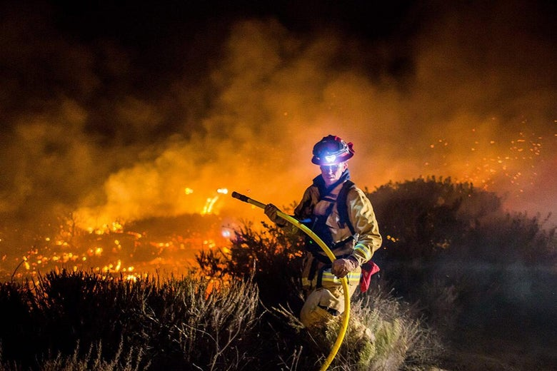 Firefighters work to extinguish the Thomas Fire as it burns past the 101 toward the Pacific Coast Highway in Ventura, California, on Thursday.