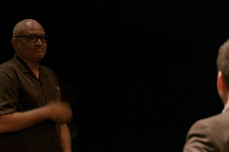 Larry Wilmore, standing against a black background in a theater.
