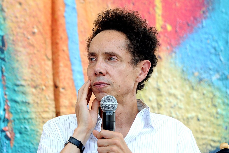 Malcolm Gladwell pondering a question while holding a microphone.