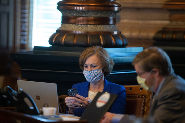 Bollier, wearing a mask, looks at her phone. Another man in a mask works at a laptop. They are seated at a table inside the ornate Capitol.