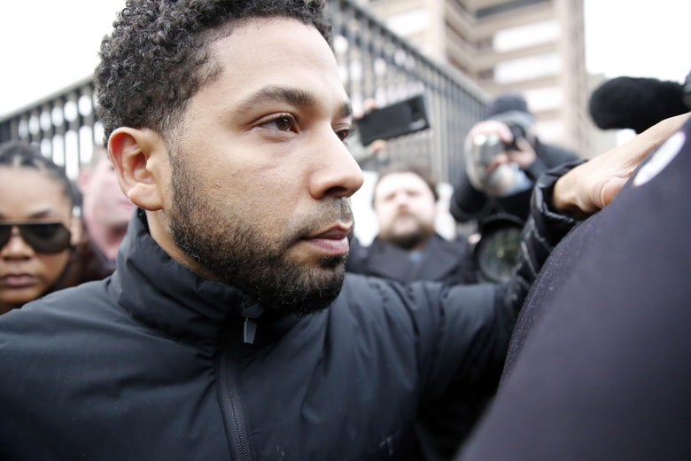 Jussie Smollett can be seen surrounded by a throng of people, some of whom have cameras.