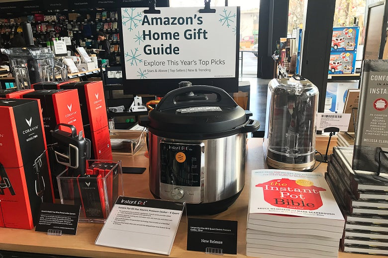 "A sign says ""Amazon's Home Gift Guide"" over an Instant Pot, other kitchen gadgets, and books."