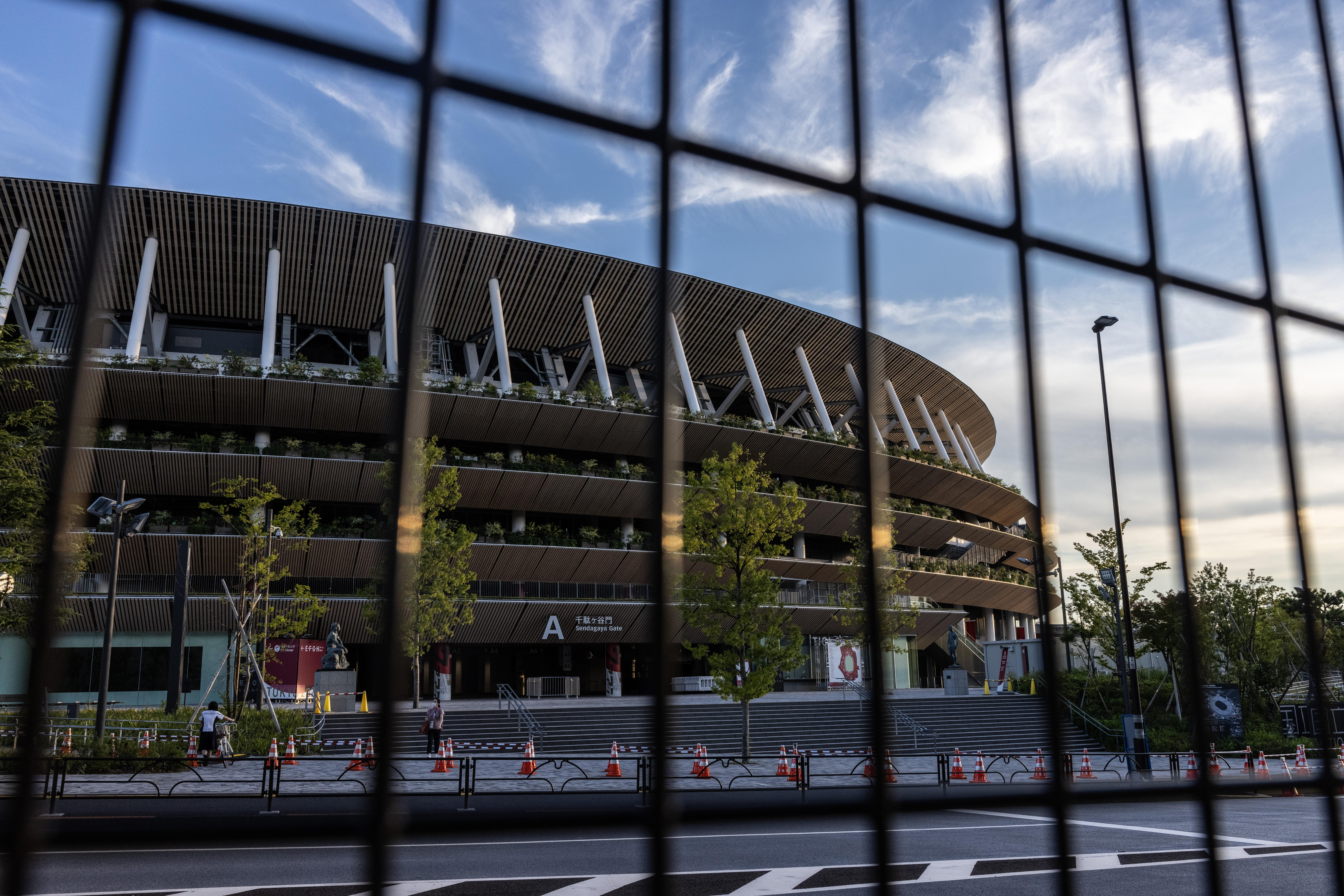 TOKYO, JAPAN - JULY 21: Tokyo Olympic stadium is pictured through a security fence on July 21, 2021 in Tokyo, Japan. With just two days until the Olympics opening ceremony, Toshiro Muto, the head of the Tokyo 2020 organising committee has stated that he will not rule out cancellation of the Games as more than seventy people associated with the event have already tested positive for coronavirus. (Photo by Carl Court/Getty Images)