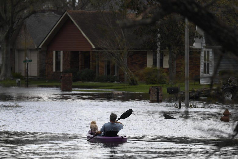 A person kayaks with a dog through flood waters past homes in LaPlace, Louisiana on August 30, 2021.