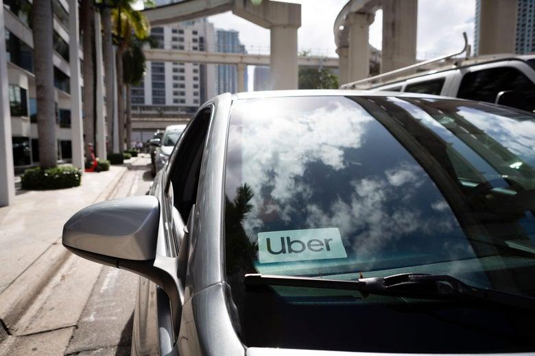 An Uber sticker is seen on a car windshield.