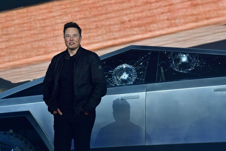 Tesla co-founder and CEO Elon Musk stands in front of the shattered windows of the newly unveiled Cybertruck.