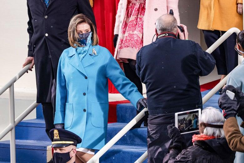 Nancy Pelosi arrives, wearing a blue jacket and mask.