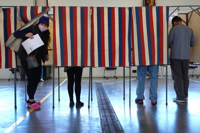 a voter coming out from behind a curtain