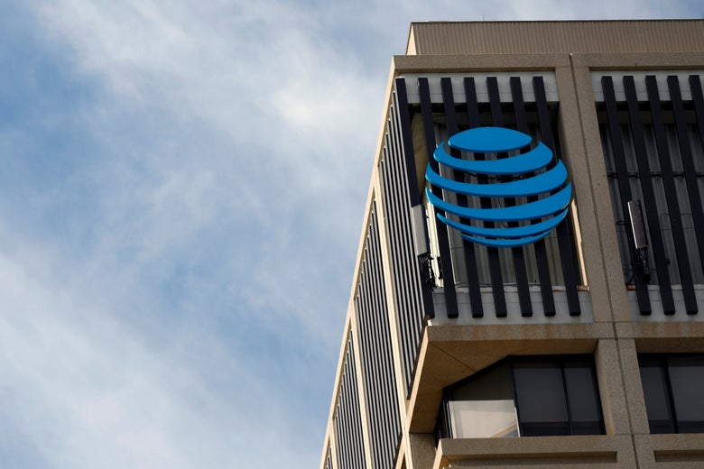 The AT&T orb logo on a building, against a blue sky.