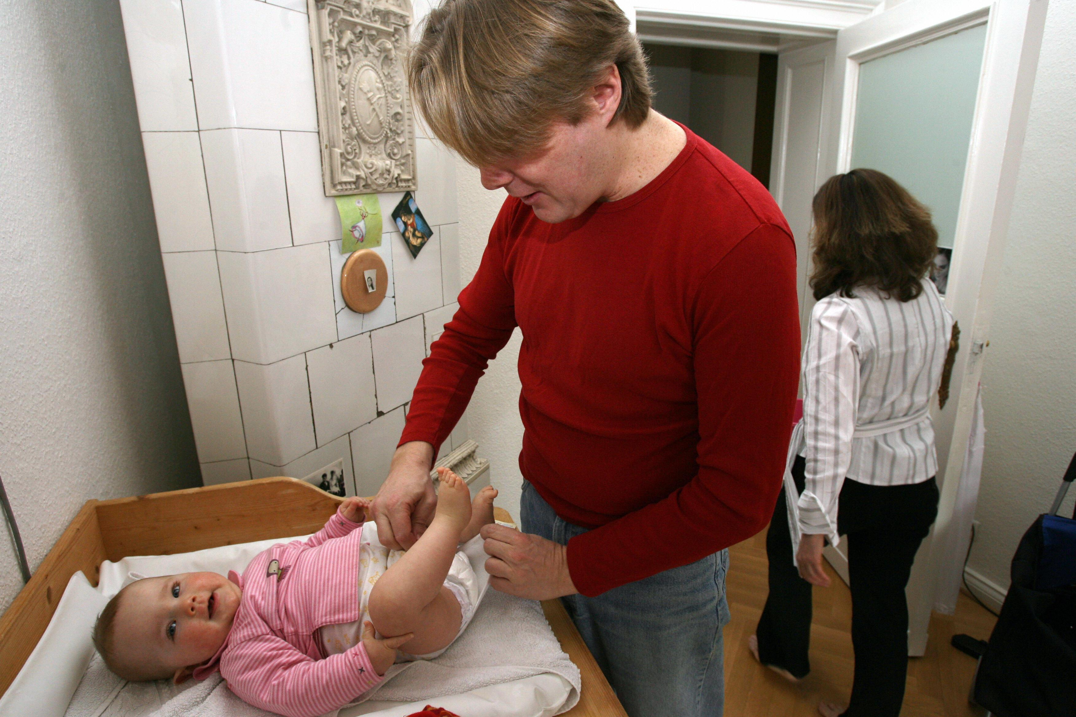 Berlin resident Nicolas W. changes his 8-month-old daughter at home 21 April 2006.