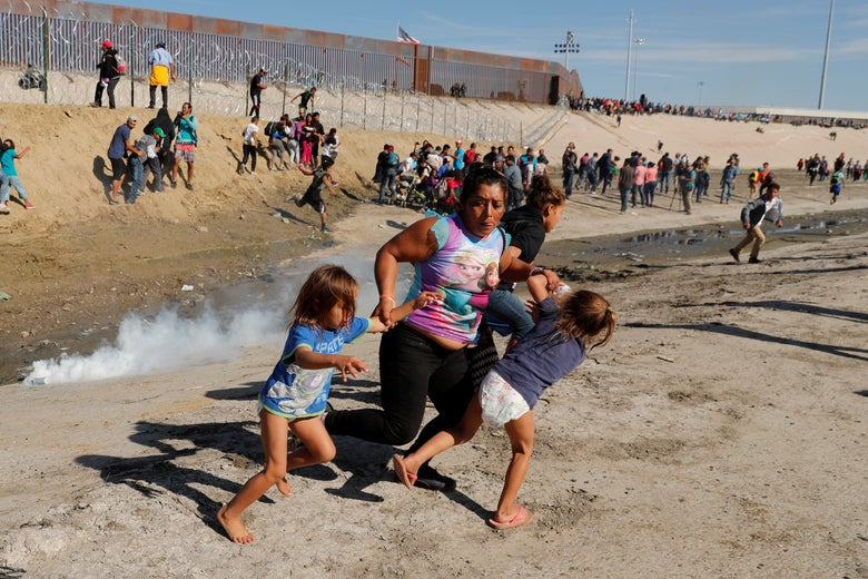 A migrant family, part of a caravan of thousands traveling from Central America en route to the United States, run away from tear gas in front of the border wall between the U.S and Mexico in Tijuana on November 25, 2018.