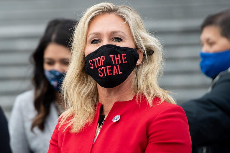 """Marjorie Taylor Greene wears a black mask with red text that says, """"STOP THE STEAL."""""""