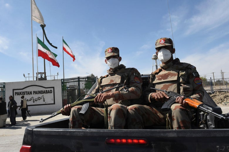 Pakistani soldiers wearing face masks hold guns while sitting in the back of a pickup truck.