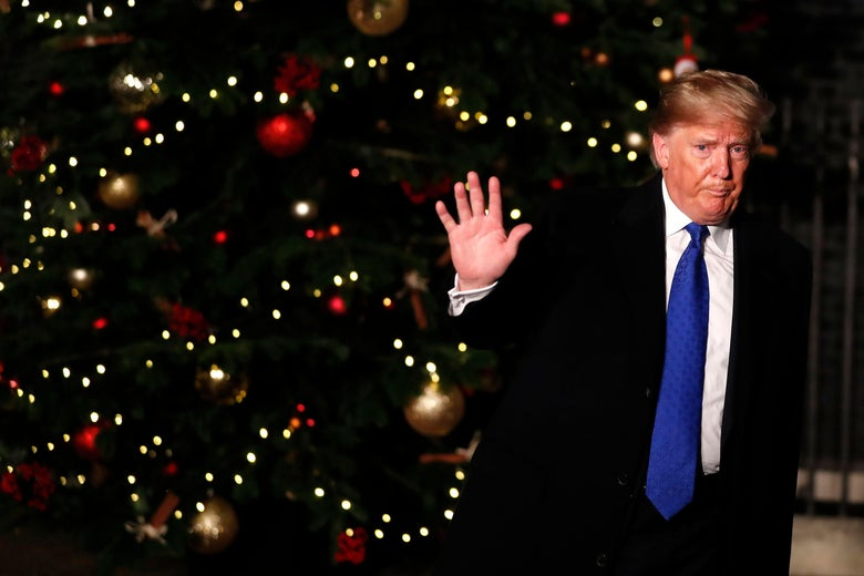 Trump is standing in front of a Christmas tree, waving goodbye, with a neutral or negative facial expression