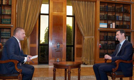 Syria's President Bashar al-Assad (R) speaks during an interview with Russian state television RU24 in Damascus.