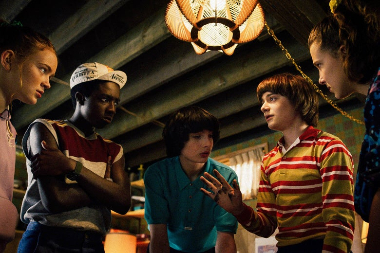 The teen protagonists of Stranger Things huddle in a circle below a lamp.