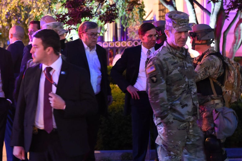 Barr and Esper in suits surrounded by uniformed military.