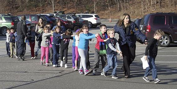 In this photo provided by the Newtown Bee, Connecticut State Police lead children from the Sandy Hook Elementary School in Newtown, Conn., following a reported shooting there Friday, Dec. 14, 2012.