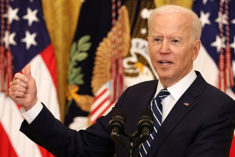 Biden, seen at a lectern against a backdrop of American and presidential-seal flags, gestures with his right hand and thumb.